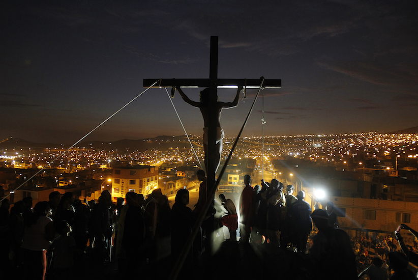 An actor hangs from a cross during the re-enactment of the crucifixion of Jesus Christ during Holy Week at Mi Peru